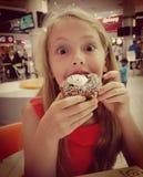 Blondes kleines Mädchen, das Donut isst Lizenzfreie Stockfotos
