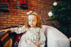 Blondes kleines Mädchen, das durch den Weihnachtsbaum sitzt Stockbild