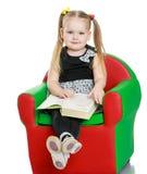 Blondes kleines Mädchen, das ein Buch sitzt auf liest Lizenzfreie Stockfotografie