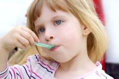 Blondes kleines Mädchen, das Eiscremeportrait isst Stockfotos