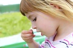 Blondes kleines Mädchen, das Eiscremeportrait isst Lizenzfreie Stockfotografie