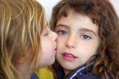 Blondes kleines Mädchen, das ihre blauen Augen der Tochter küßt Stockbilder