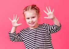 Blondes kleines Mädchen, das ihre Palmen zeigt Lizenzfreie Stockbilder