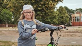 Blondes kleines Mädchen, das mit ihrem Fahrrad im Sommer in der Stadt aufwirft stock footage