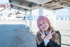 Blondes kleines Mädchen, das Sieggeste am Strand tut Lizenzfreie Stockfotografie