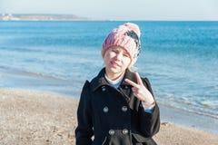 Blondes kleines Mädchen, das Sieggeste am Strand tut Stockfoto