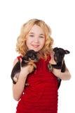 Blondes kleines Mädchen, das zwei Welpen tragen rotes Kleid hält Lizenzfreies Stockfoto