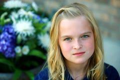 Blondes kleines Mädchen durch Blumen Stockbilder