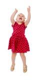 Blondes kleines Mädchen in einem roten Tupfenkleid springt Stockfoto
