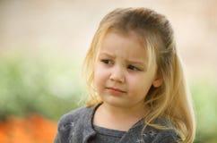 Blondes kleines Mädchen in einer grauen Strickjacke Lizenzfreie Stockfotos