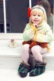 Blondes kleines Mädchen in gestricktem Strickjackesitzen Lizenzfreies Stockfoto