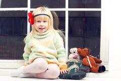 Blondes kleines Mädchen in gestrickter Strickjacke Stockbilder
