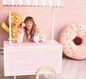 Blondes kleines Mädchen mit Süßigkeit Stockfotografie