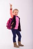 Blondes kleines Mädchen mit Schultasche auf der Rückseite, Punkte mit dem Finger in der Luft Lizenzfreie Stockfotos