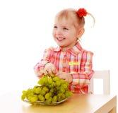 Blondes kleines Mädchen, welches die Trauben sitzen an isst Lizenzfreies Stockfoto
