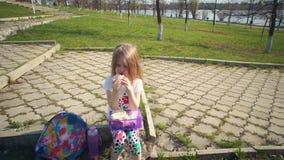Blondes kleines M?dchen, das ihr Mittagessen im Park am sonnigen Tag isst stock video