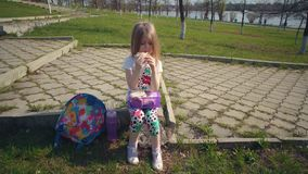 Blondes kleines M?dchen, das ihr Mittagessen im Park am sonnigen Tag isst stock footage