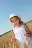 Blondes kleines Mädchen, das auf dem Weizengebiet steht Lizenzfreie Stockfotos