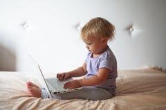 Blondes Kleinkind, das zu Hause mit PC-Laptop, zuhause spielt Lizenzfreies Stockbild