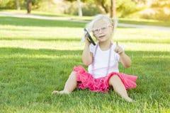 Blondes Kleinkind-Mädchen, das draußen am Handy spricht Stockbild