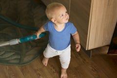 Blondes Kleinkind, welches die Küche mit Staubsauger aufräumt Stockfotografie