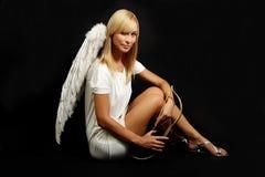 Blondes Kupid/weißer Engel auf schwarzem Hintergrund Stockfotos