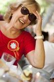 Blondes Lächeln der älteren Frau, ein rotes Hemd tragend stockfotos