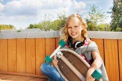 Blondes lächelndes Mädchen mit Kopfhörern und Skateboard Stockbild