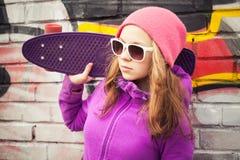 Blondes lächelndes Mädchen steht nahe einer Wand mit Skateboard Stockbilder
