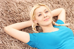 Blondes lächelndes weibliches Lügen auf einem Teppich Lizenzfreies Stockfoto