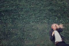 Blondes Lügen auf dem Gras Porträt der Frau in der modernen schwarzen Lederjacke Lizenzfreie Stockfotos