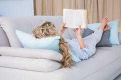 Blondes Lügen auf der Couch, die ein Buch liest Stockbild