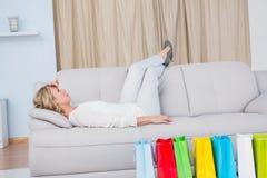 Blondes Lügen auf der Couch, die Kopfschmerzen erhält Lizenzfreie Stockfotografie
