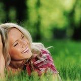 Blondes Lügen auf grünem Gras Stockbild