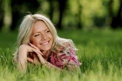 Blondes Lügen auf grünem Gras Lizenzfreies Stockbild