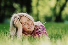 Blondes Lügen auf grünem Gras Lizenzfreie Stockbilder