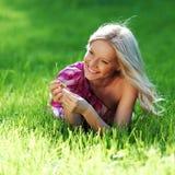 Blondes Lügen auf grünem Gras Lizenzfreie Stockfotografie