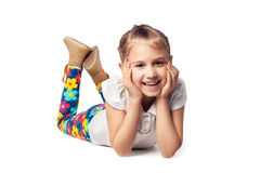 Blondes Lachen des kleinen Mädchens, liegend auf seinem Magen Stockfotos