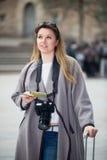 Blondes lachendes Mädchen, das Broschüre in den Händen hält Lizenzfreie Stockfotografie