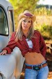 Blondes Landmädchen im Hut und in den Jeans Lizenzfreies Stockbild