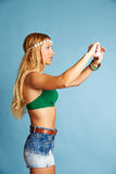 Blondes langes Haarmädchen mit Foto selfie der kurzen Jeanshose Stockfotos