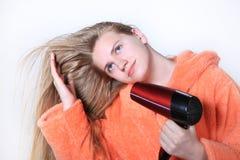 Blondes langes Haartrockenes des Mädchens unter Verwendung des hairdryer Stockbilder