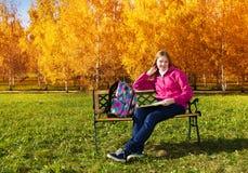 Blondes langes Mädchen im Park nach der Schule Stockfoto