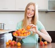 Blondes langhaariges Mädchen, das Aprikosen in der Hauptküche hält Stockbilder