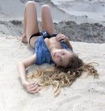 Blondes langhaariges Mädchen, das auf Sand liegt und Kamera betrachtet Lizenzfreies Stockbild