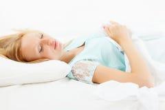 Blondes langhaariges Mädchen, das auf weißem Kissen schläft Stockbild
