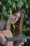 Blondes langhaariges Mädchen, das eine Akustikgitarre spielt Stockfotografie