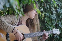 Blondes langhaariges Mädchen, das eine Akustikgitarre spielt Stockfotos