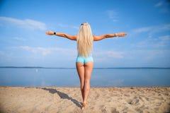 Blondes langhaariges Mädchen in einer blauen Klage ist, tuend im Sonnenlicht ausdehnend und Yoga auf einem reizenden Strand des a Lizenzfreie Stockbilder