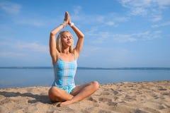 Blondes langhaariges Mädchen in einer blauen Klage ist, tuend im Sonnenlicht ausdehnend und Yoga auf einem reizenden Strand des a Stockbild